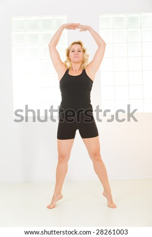 Elder woman dressed sportswear working out. She's looking at camera. Front view.