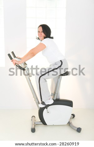 Elder woman exercising on bike. She's smiling and looking at camera. Side view.