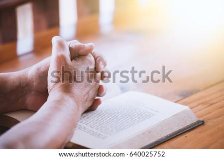 elder woman hands folded in...