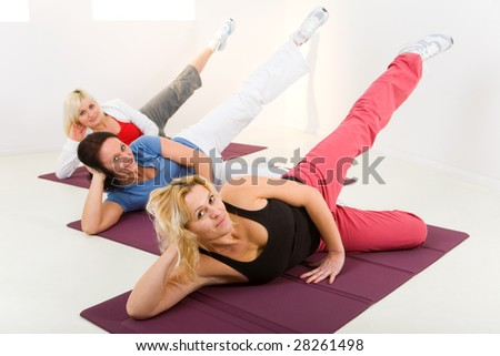 Elder women during exercising on mat. They're smiling and looking at camera.