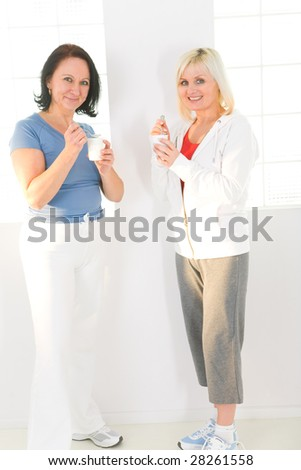 Elder women eating yoghurt and talking. They're smiling and looking at camera