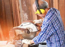 Elderly Asian carpenter craftsman use circular saws to process wood for furniture. Carpenter wears safety gloves and soundproof earmuffs, with a pile of wood behind them