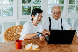 Elderly Asian couple in personal protective face shield sitting at table at home. Senior man and woman with PPE using laptop and credit card while making online shopping during coronavirus pandemic.