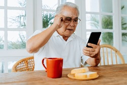 Elderly Asian male having eyesight problems and wearing eyeglasses while gazing and reading message on smartphone during breakfast at home. Old man having eye blurred vision indoors.