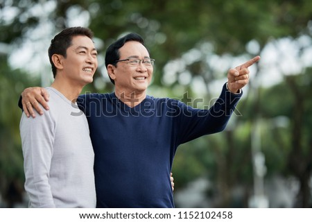 Elderly Asian man smiling and pointing at distance while embracing son on blurred background of park