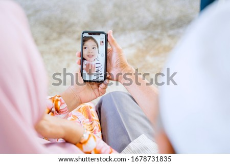 Elderly Asian muslim couple holding a phone, while video calling their playful granddaughter in their home