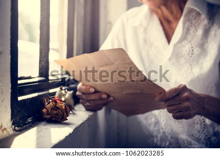Elderly asian woman sitting thoughful with old letters in her hands