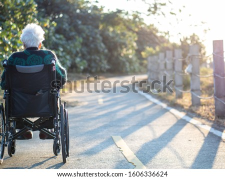 Elderly Asian women, elderly, sit on wheelchairs outdoors