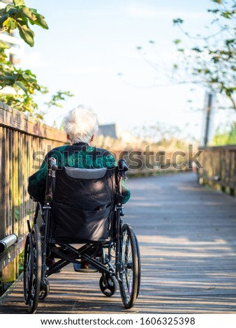 Elderly Asian women, elderly, sit on wheelchairs outdoors in the park.