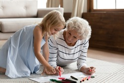 Elderly babysitter teach little girl drawing lying on warm floor, helping improve creative abilities, develop artist talent. Caring old 50s grandma spend time with small granddaughter at modern home