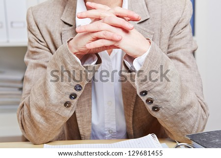 Elderly business woman crossing her hands at her desk in the office