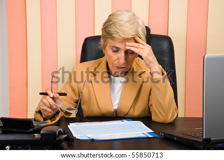 Elderly business woman having problems with graphics or a bad head ache looking down,she sitting  on chair at desktop - stock photo