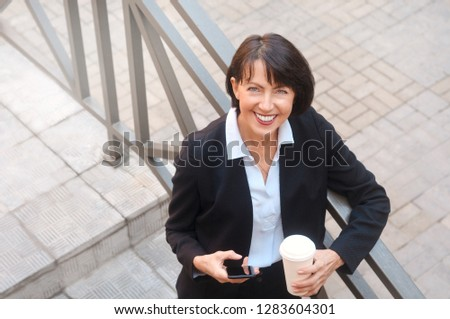 Elderly business woman with coffee using cell phone, outdoor. Work anywhere concept. stock photo