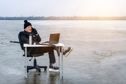 elderly businessman in suit and skates holds hockey stick, talking on sell phone, works with laptop on table in the middle of a frozen lake. Customer support concept, twenty-four seven, copy space