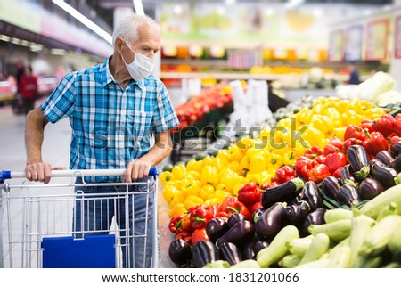 elderly caucasian man in mask with covid protection choosing season vegetables in supermarket department ストックフォト ©