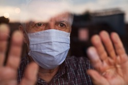 Elderly caucasian man wearing hand made protective face mask,in nursing care home,looking outside window, sadness,stress  hope in his eyes,self isolation due to global COVID-19 Coronavirus pandemic
