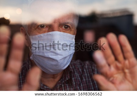 Elderly caucasian man wearing hand made protective face mask,in nursing care home,looking outside window, sadness,stress & hope in his eyes,self isolation due to global COVID-19 Coronavirus pandemic