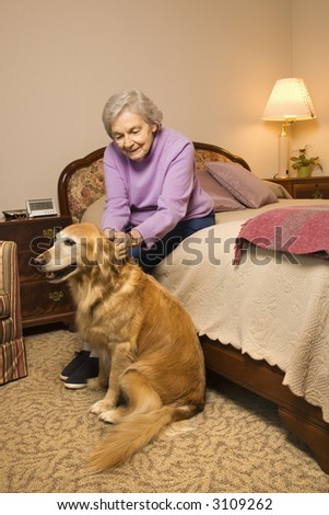 Elderly Caucasian woman and dog in bedroom at retirement community center.