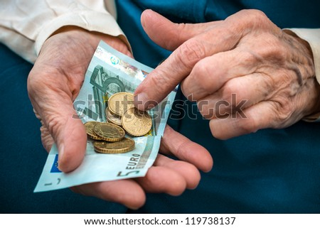 elderly caucasian woman counting money in her hands