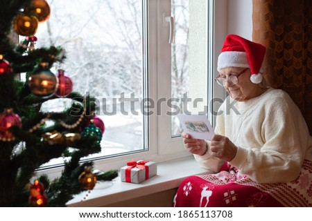 Elderly Caucasian woman Santa hat sits window with glasses her face and reads greeting card.Christmas eve, gift, Christmas tree.Concept: Christmas holidays, New Year, caring for elderly, the lonely