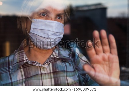 Elderly caucasian woman wearing hand made protective face mask, in nursing care home, looking outside window with sadness in her eyes, self isolation due to the global COVID-19 Coronavirus pandemic