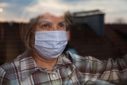 Elderly caucasian woman wearing handmade protective face mask,nursing care home,looking outside the window with sadness in her eyes,self isolation due to the global COVID-19 Coronavirus pandemic,hope