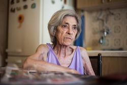 Elderly caucasian 80 years old woman sitting at kitchen table,sad facial expression,having the look of uncertainty, melancholy,nostalgia or sadness, insecure retirement life concept, Coronavirus COVID