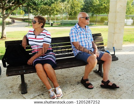Elderly couple are sitting upset on a bench in a park . Family quarrel.
