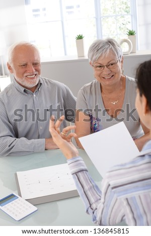 Elderly couple at financial consultation, smiling.