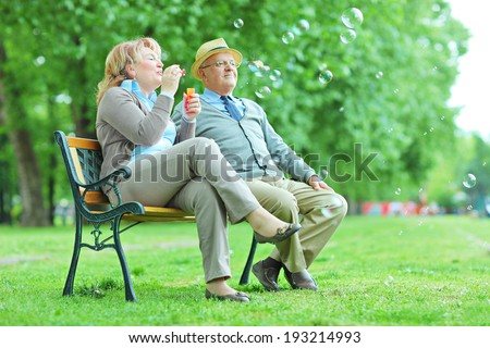 Elderly couple blowing bubbles in park seated on bench