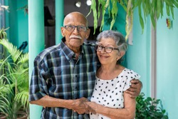 Elderly couple embracing and smiling looking at the camera