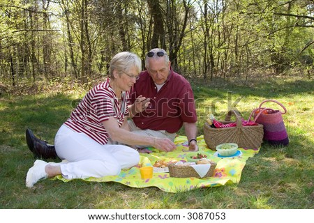 Elderly couple enjoying a sunday afternoon with a picnic (focus on man and some movement in the woman moving forward)