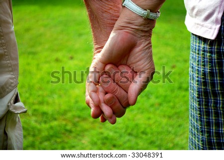 elderly couple holding hands in front of green grass