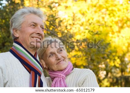 elderly couple in a autumn park - stock photo
