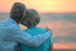 Elderly couple in love at sunset on a summer evening watching sea