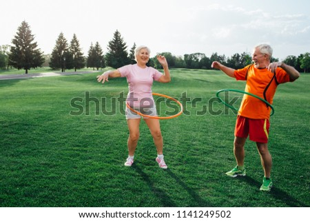 elderly couple in park practising with hoops, have fun and enjoy the rest. Hooping workout #1141249502