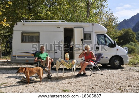Elderly couple is traveling by motor home - stock photo