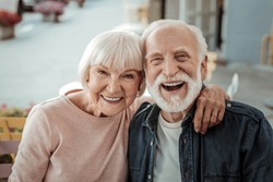 Elderly couple. Joyful nice elderly couple smiling while being in a great mood