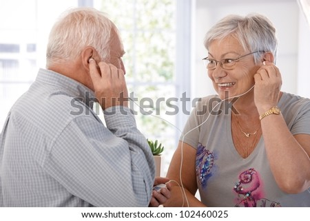 Elderly couple listening to music on mp3 player, smiling. - stock photo