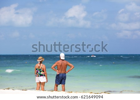 Elderly couple looking at the sea. The adults are standing on the beach of the Caribbean sea. People composed to the left. Turquoise water and white sand. #621649094