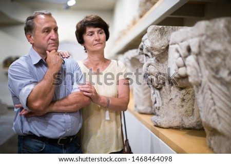 elderly couple of european tourists view exhibits in museum