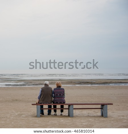 Elderly couple on the beach sitting on the bench.