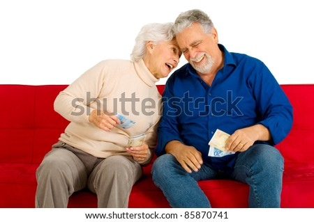 elderly couple on the couch with money in hand - stock photo