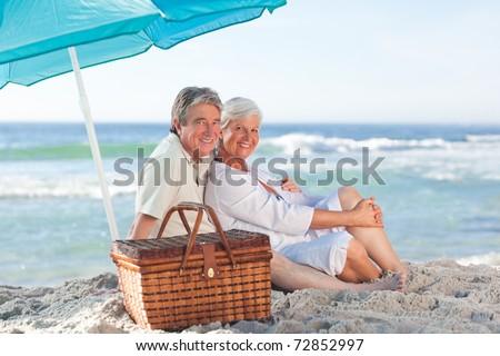 Elderly couple picniking on the beach - stock photo