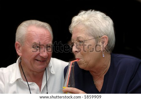 elderly couple, seniors still in love, woman drinking, man smiling. Love, romance, marriage concept. - stock photo