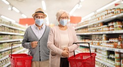 Elderly couple shopping in a supermarket and wearing medical face masks