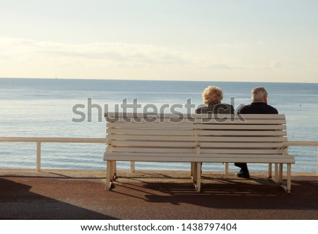 Elderly couple sitting on a bench overlooking the sea on a nice afternoon in Nice of France.  #1438797404