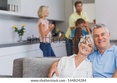 Elderly couple sitting on the couch and smiling at camera while their family is standing in the kitchen behind