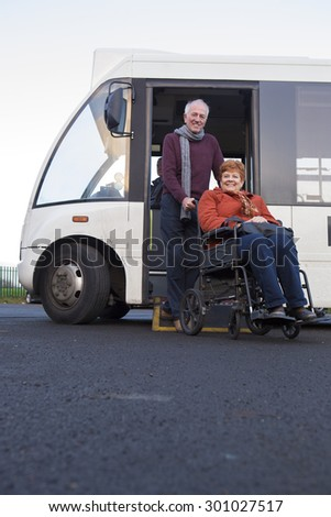 Elderly couple smiling for the camera as they get off the bus. The man is pushing his wheelchair bound wife.