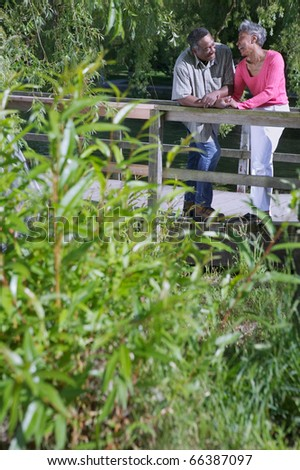 Elderly couple standing together leaning on a wooden railing in a park - stock photo